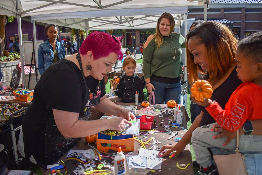 A woman working with craft supplies as a woman holding a young girl looks on.