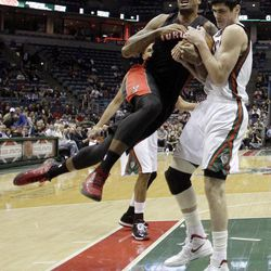 Toronto Raptors' James Johnson and Milwaukee Bucks' Ersan Ilyasova, right, battle for a loose ball during the first half of an NBA basketball game Monday, April 23, 2012, in Milwaukee.