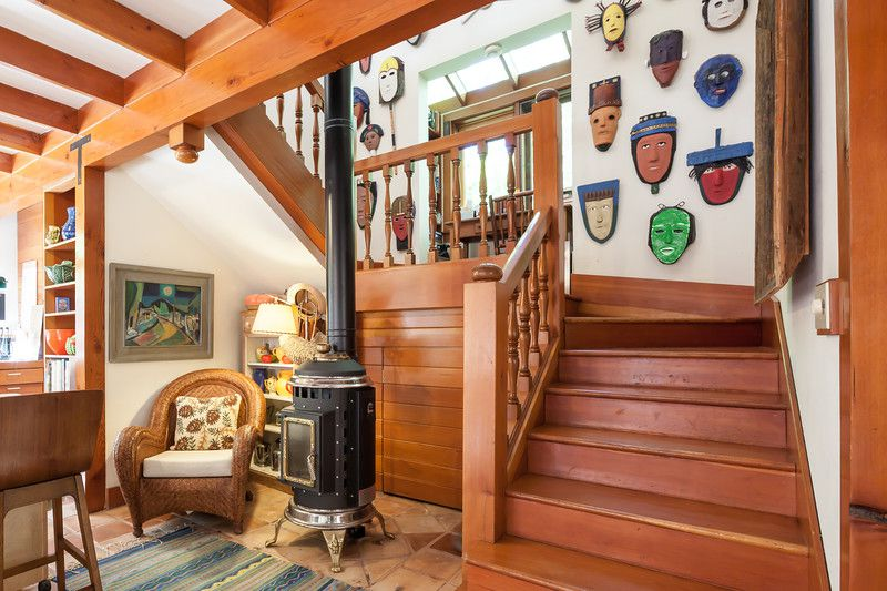 A large mask collection is hung on the stairwell wall of Joyce Maynard's Lafayette home.