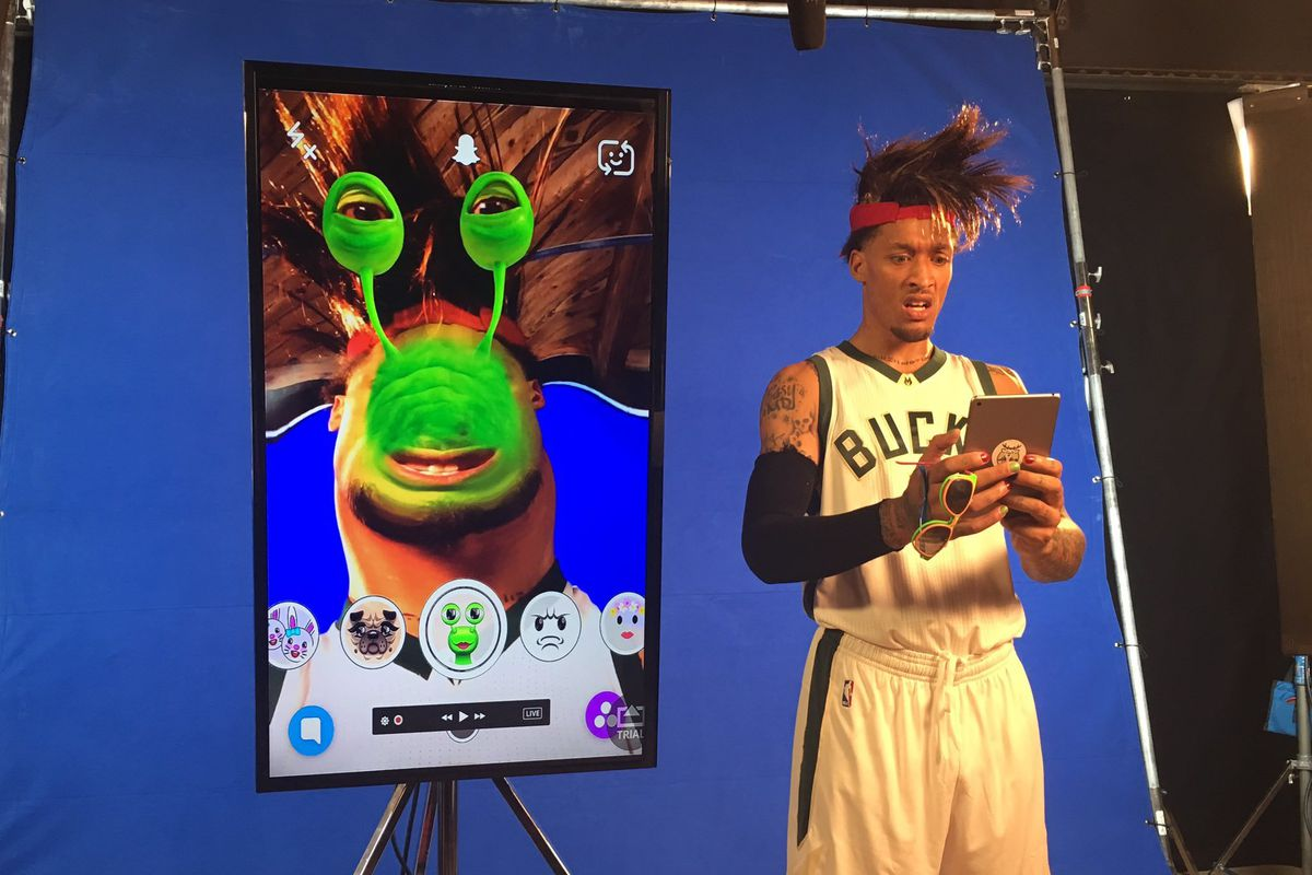 Michael Beasley is holding an iPad at Bucks media day and the screen behind him shows his face turning into a slug face with a snapchat filter. Beas looks confused and his hair is wild. The slug looks happy tho.