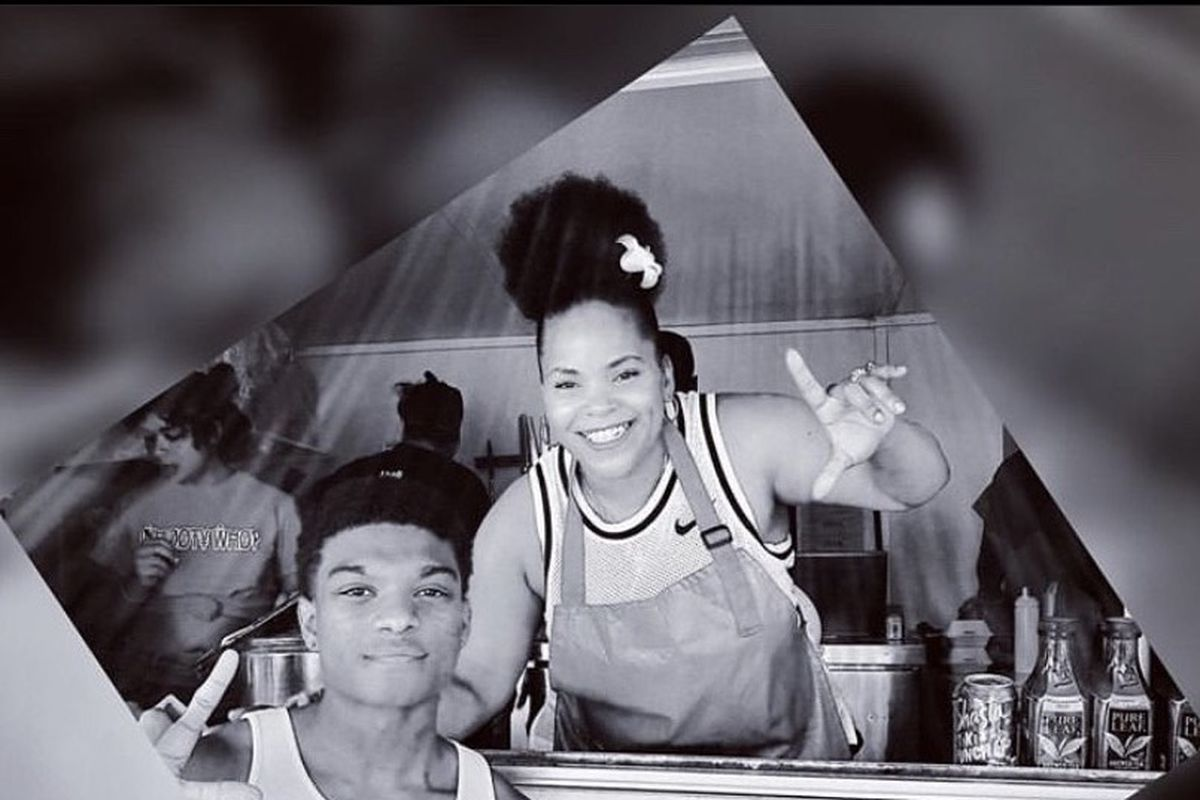 """Kiauna Nelson, a black woman, holds up a """"L"""" with her fingers standing in her cart. A young man stands with her from outside the cart"""