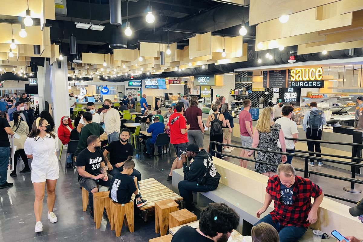 A crowd of people gather inside a busy food hall on Causeway Street in Boston, adjacent the TD Garden