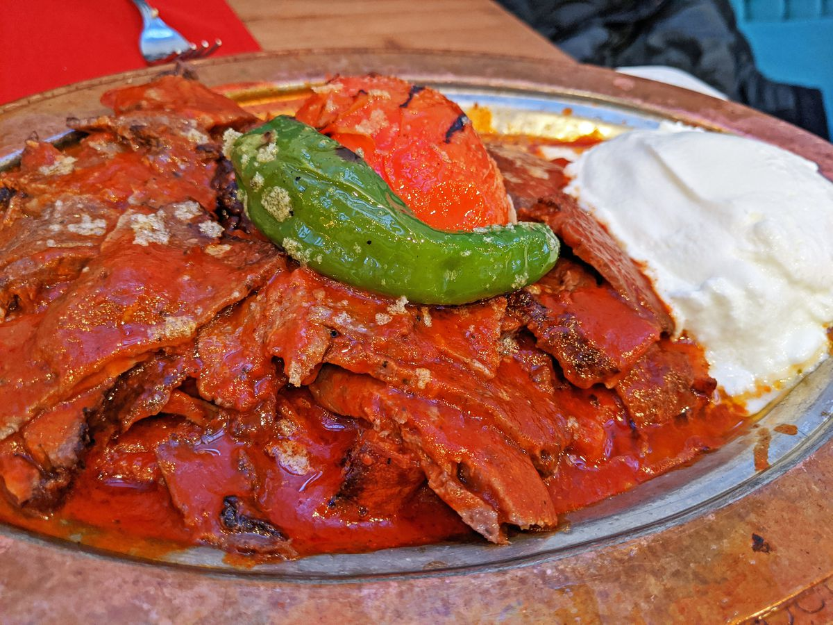 A heap of meat covered in red sauce with a reservoir of yogurt beside it.