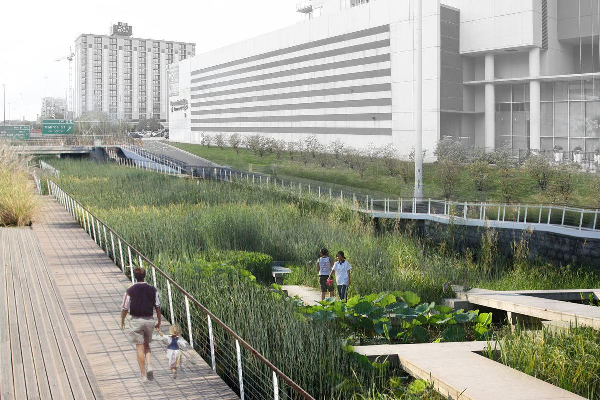 A park filled with native prairie grasses between roadway bridges, surrounded by taller buildings.