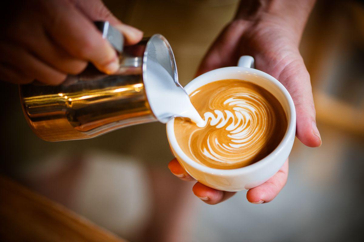 A barista pours latte art into a white ceramic mug.