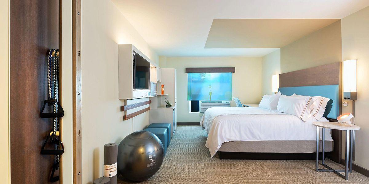 A hotel room features a bed with white sheets, as well as an exercise ball, yoga mat, and more fitness equipment.