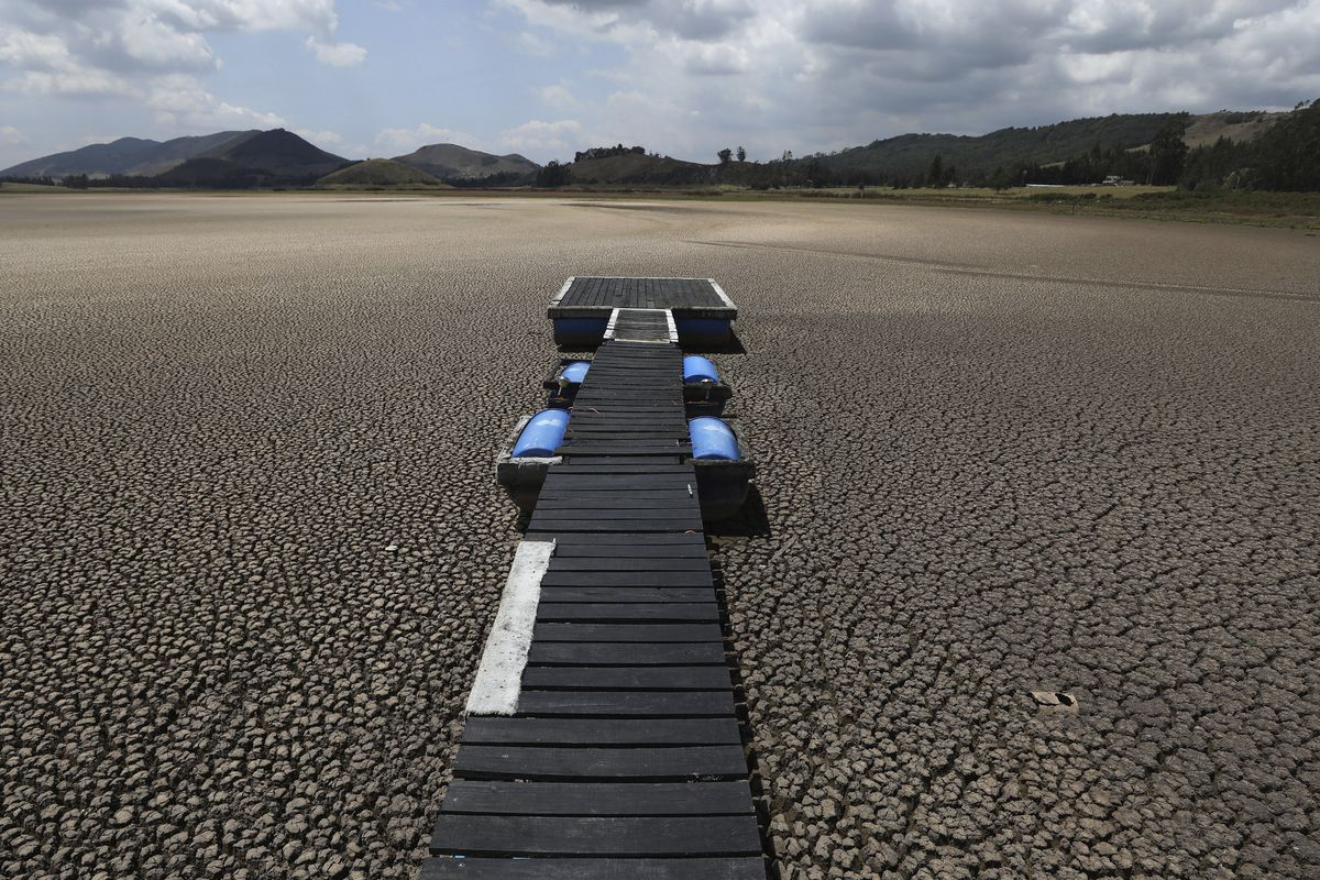 In this Wednesday, Feb. 17, 2021 file photo, a floating dock sits on the lakebed of the Suesca lagoon, in Suesca, Colombia. The lagoon, a popular tourist destination near Bogota that has no tributaries and depends on rain runoff, has radically decreased its water surface due to years of severe droughts in the area and the deforestation and erosion of its surroundings.