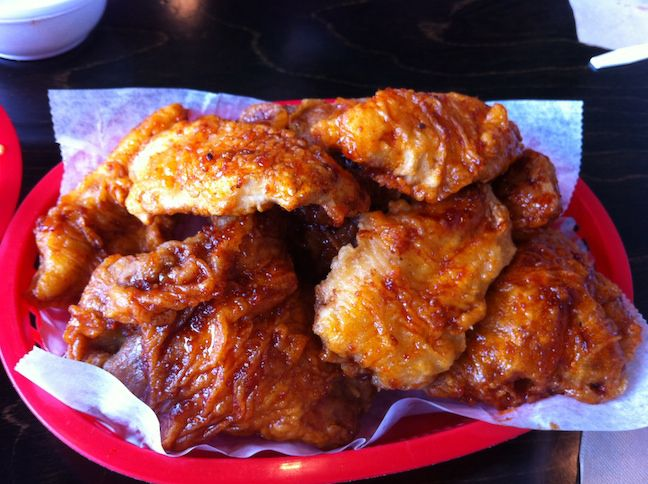 A pile of Korean fried chicken in a red plastic basket lined with wax paper.