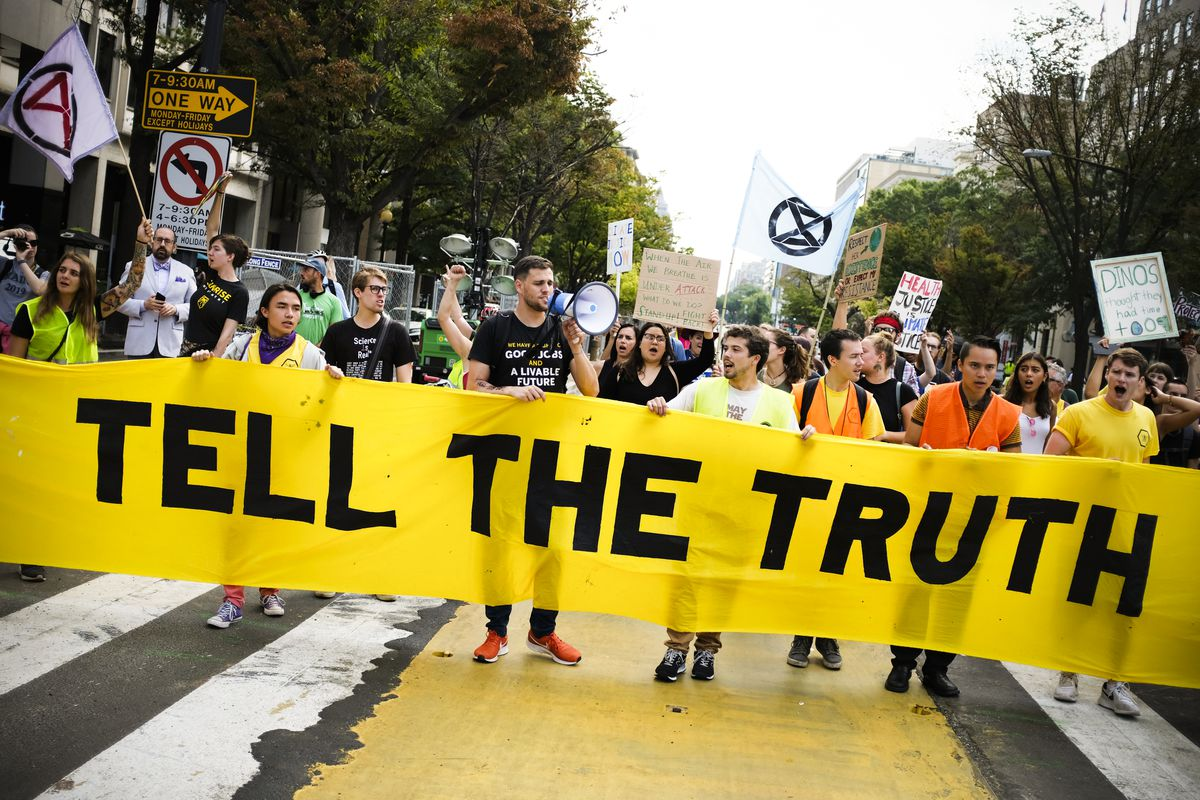 "Climate protestors march down a street in Washington, DC, carrying a banner that reads, ""Tell the truth."""