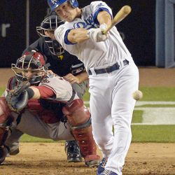 Los Angeles Dodgers' Mark Ellis, right, hits a two RBI single as Arizona Diamondbacks catcher Miguel Montero catches during the fifth inning of their baseball game, Friday, Aug. 31, 2012, in Los Angeles.