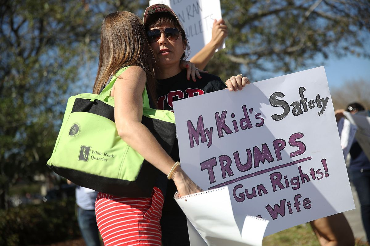 A woman whose daughter was in Marjory Stoneman Douglas HighSchool in Parkland, Fla., during the shooting on February 14 protests with others on February 17