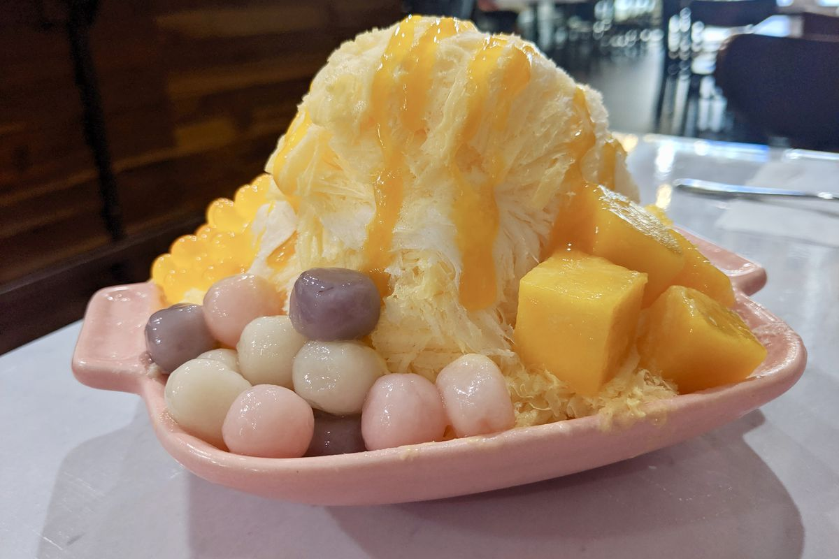 A picture of a mound of fruit-infused milky ice with mochi, mango, and popping mango boba