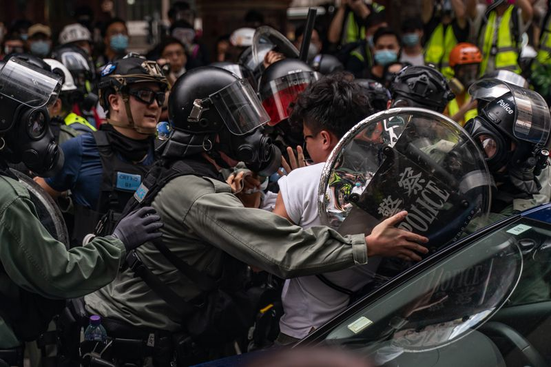 As a crowd of protesters looks on, officers in gas masks, riot helmets, and bulletproof vests surround a man in a white shirt.