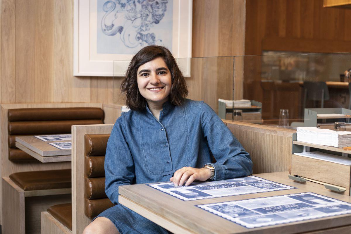 Marguerite Zabar Mariscal sitting inside a restaurant wearing a blue denim dress.