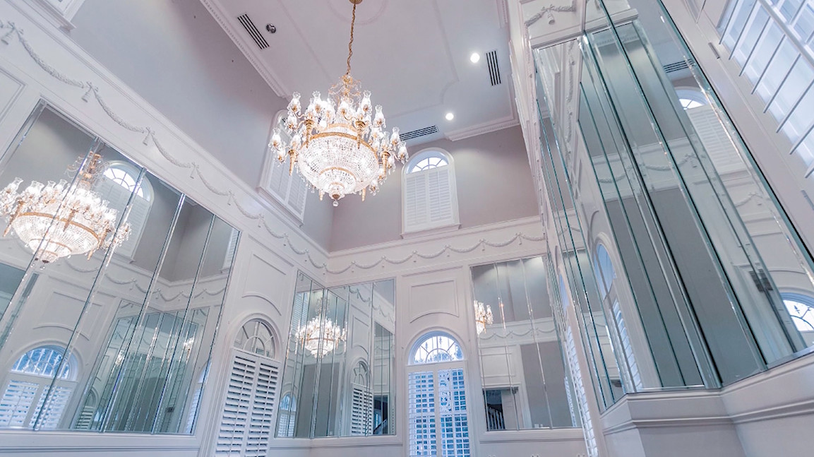 A huge white room with a chandelier above.