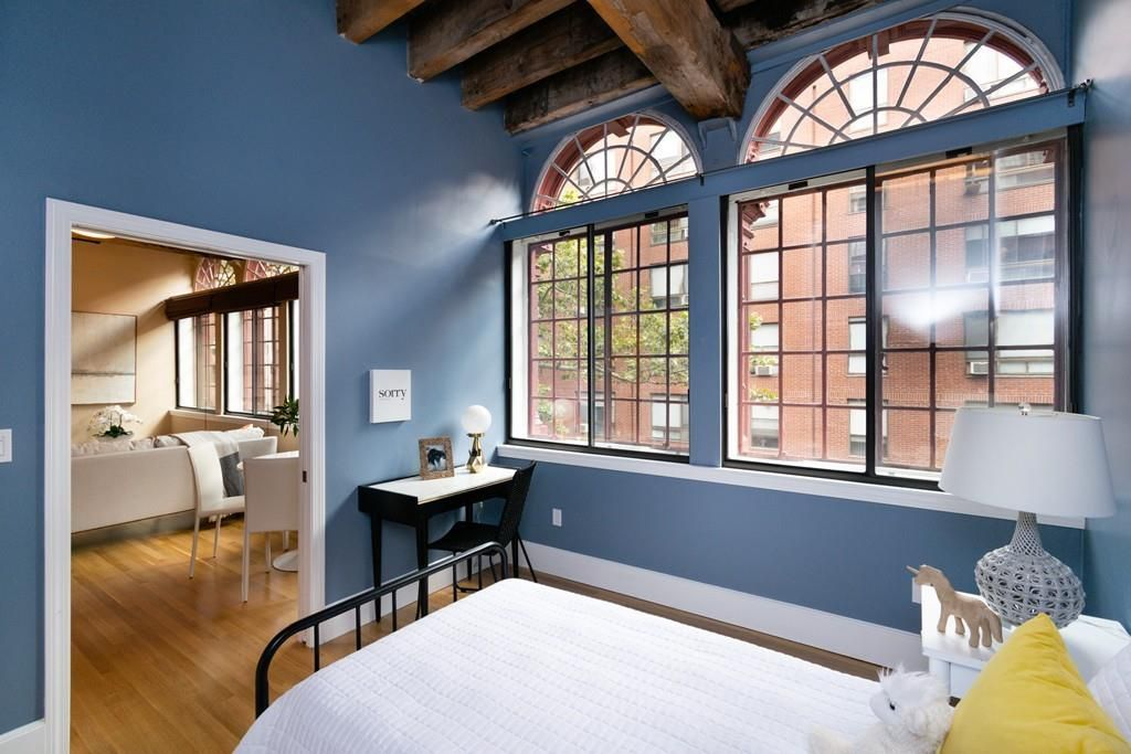 A bedroom with a bed and very large arched windows.