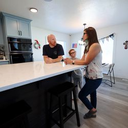 Trevor, left, Kamden and Brooke Andersen talk as they show off aspects of their Provo home that make it easier for her to live in on Wednesday, July 7, 2021. Brooke Andersen's spinal fusion surgery was delayed because of COVID-19 closures, but she finally made it to Spain during its brief opening window to have it. Now she can walk again, but she's still facing a lifetime of deterioration from her condition.