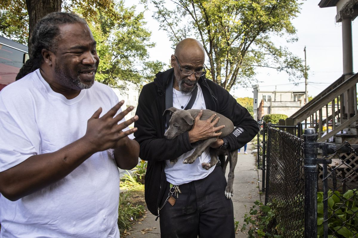 Coy Freeman, left, and his uncle Bernard Stratton look at their dogs, some of whom have burn injuries, after their home was destroyed in a fire early Thursday in the 4900 block of South Princeton Avenue in Fuller Park on the South Side.