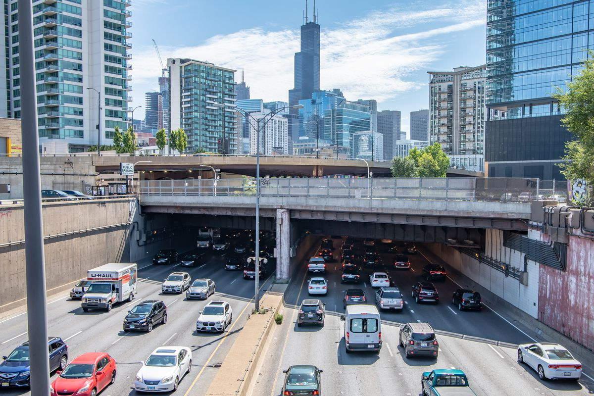 Cars on an expressway travel to a downtown center with tall towers.