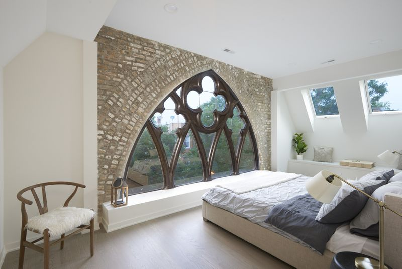 A bedroom with the white and gray bed facing an oversized arched gothic window set against a brick wall. The bed is flanked by two lamps and there's a wooden chair and house plant in the room.