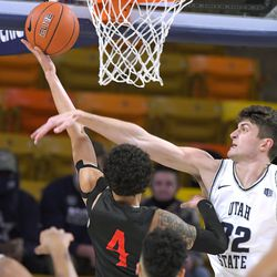 San Diego State guard Trey Pulliam (4) gets fouled by Utah State center Trevin Dorius (32) during the first half of an NCAA college basketball game Thursday, Jan. 14, 2021, in Logan, Utah.
