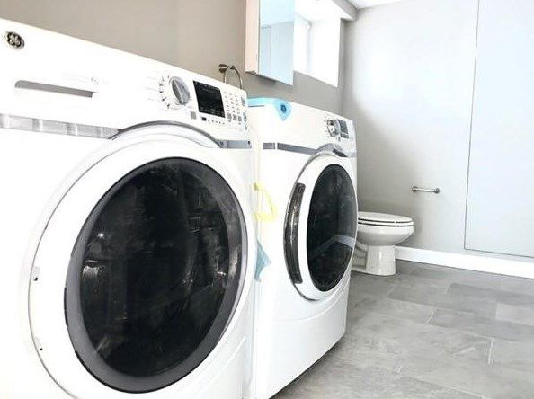 A long bathroom with a washer-dryer side by side next to a toilet.