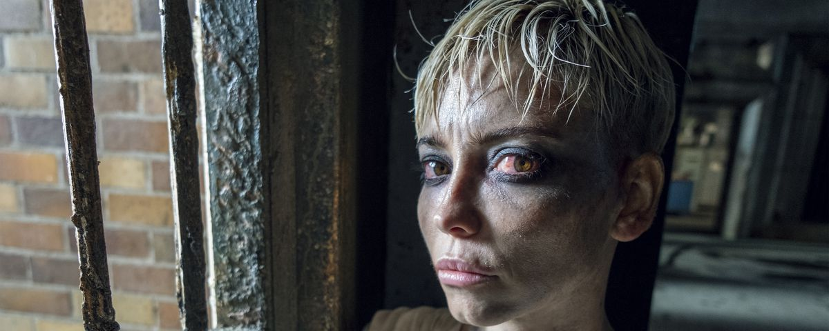 Marama Corlett as Corporal Angua stands in front of a barred window and looks at the camera with extremely bloodshot eyes in The Watch