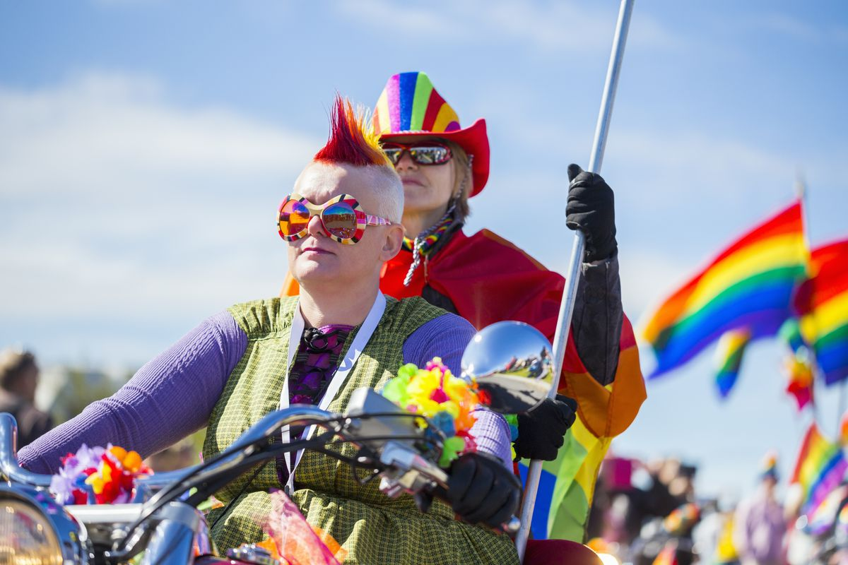 Two rainbow-festooned white adults on a bike or motorcycle with marchers and rainbow flags in background.