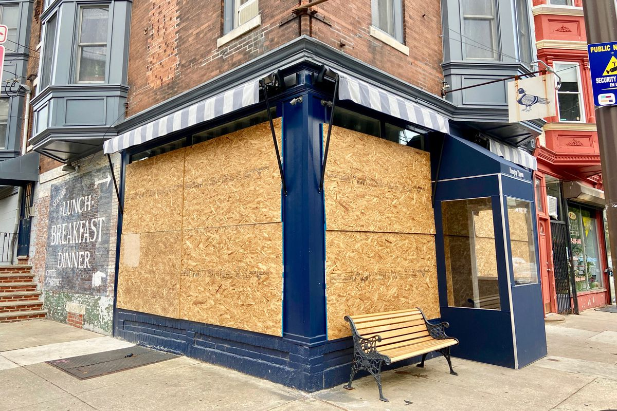 corner restaurant boarded up with plywood with a sign that shows a pigeon