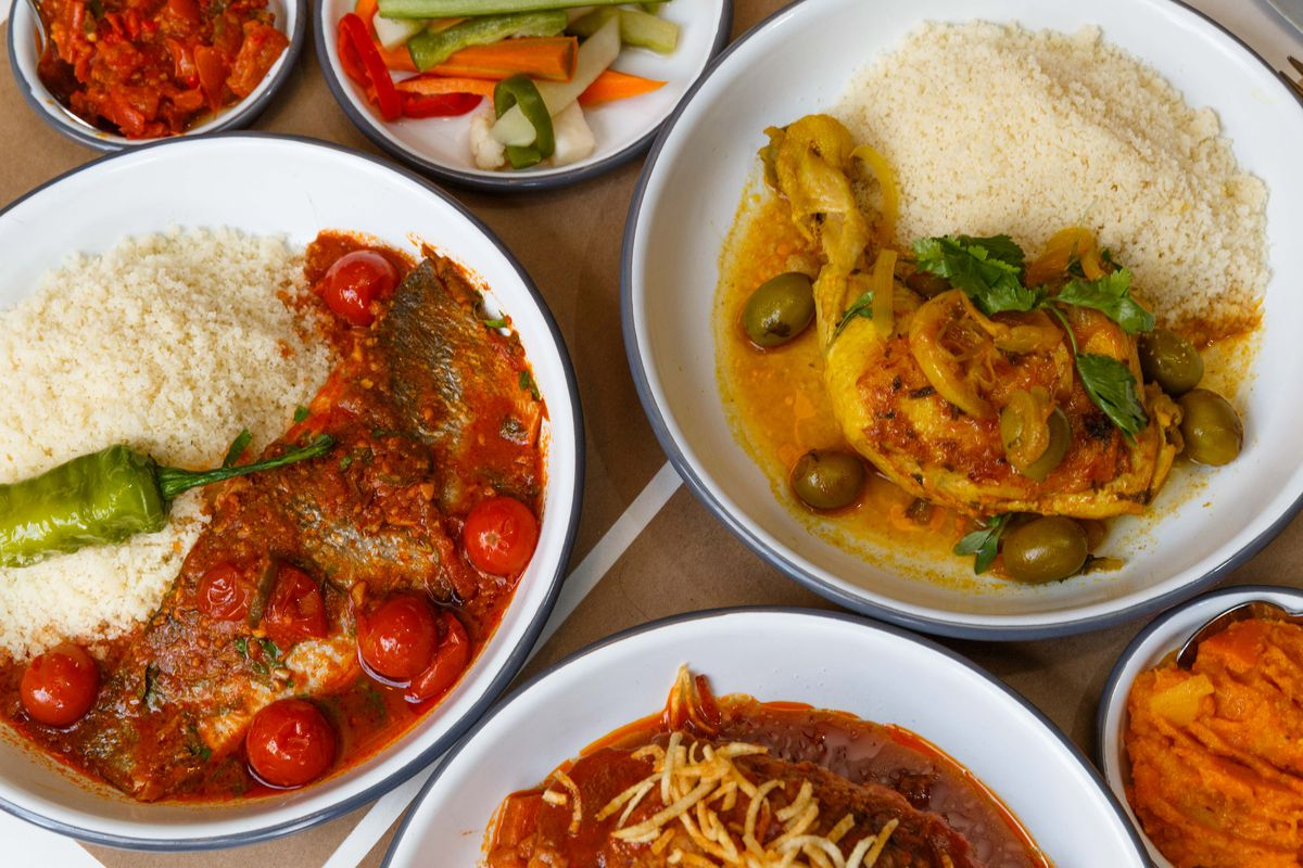 A variety of white plains contain different colored foods, some green olives can be seen in a few dishes along with piles of white couscous.