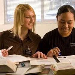 Two sister missionaries hold companionship scripture study.
