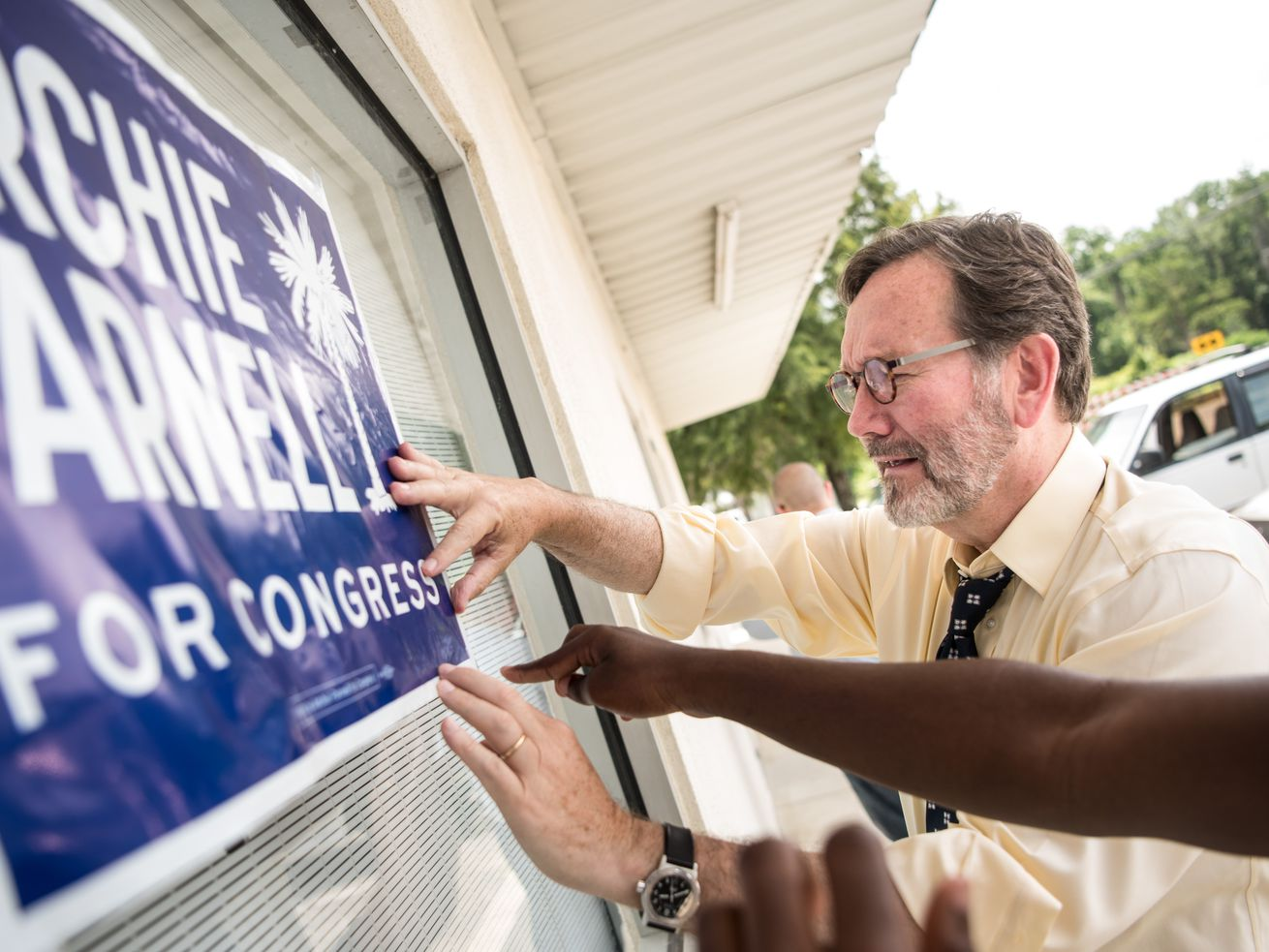 Democratic congressional candidate Archie Parnell hangs up a sign.