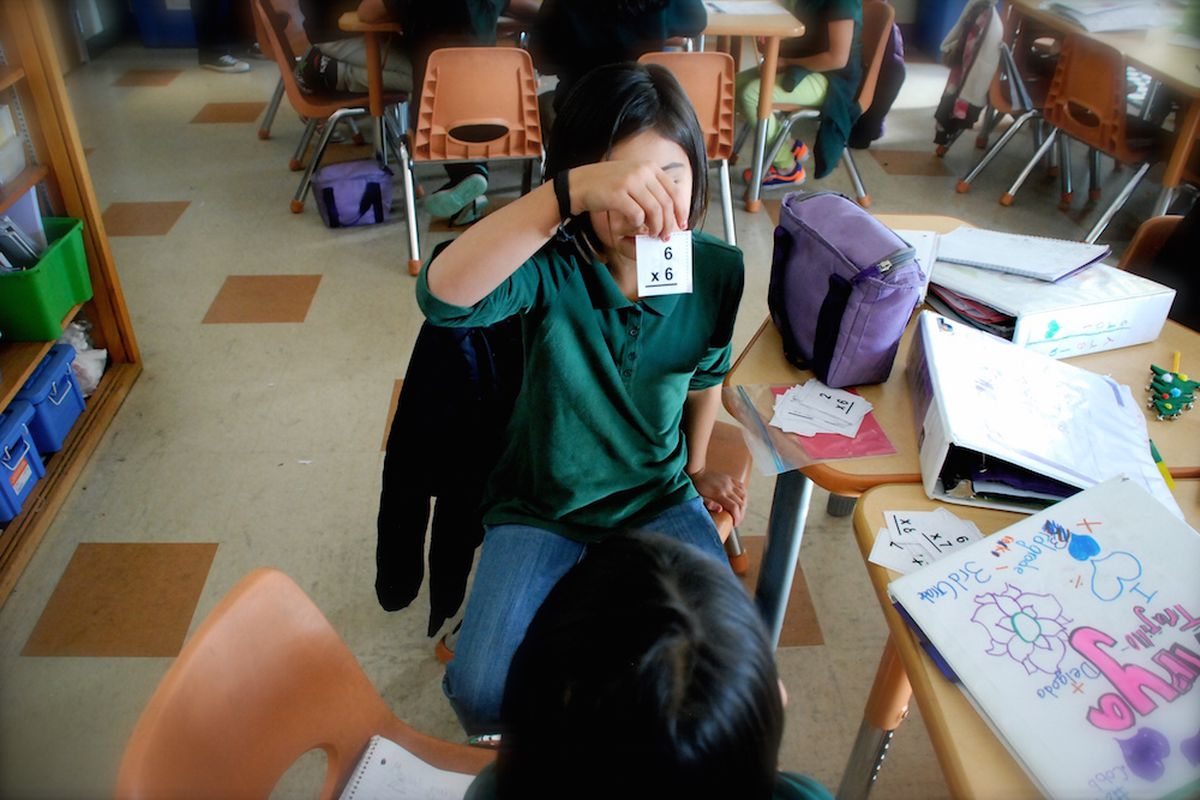 A student wearing a green polo shirt holds up a math flashcard showing the problem 6 x 6 for a classmate. The student is seated and their face is obscured by the card.