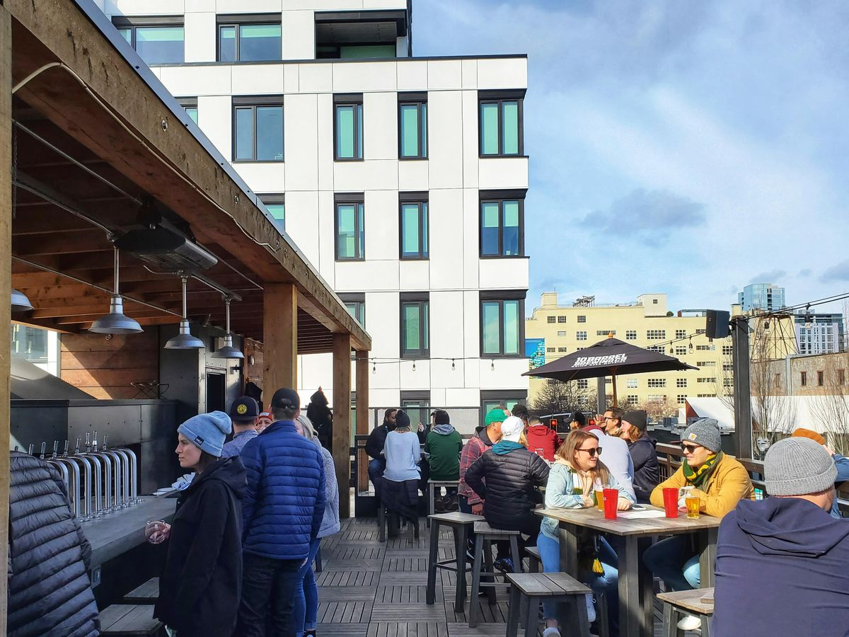 People seated at tables and standing at bar on a rooftop patio