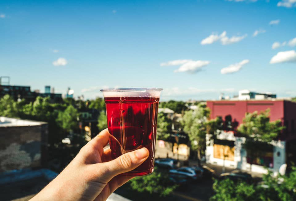 A hand holds a raspberry sour beer up over the Lyn/Lake neighborhood