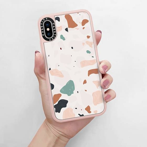 A terrazzo-patterned phone case held in a woman's hand.