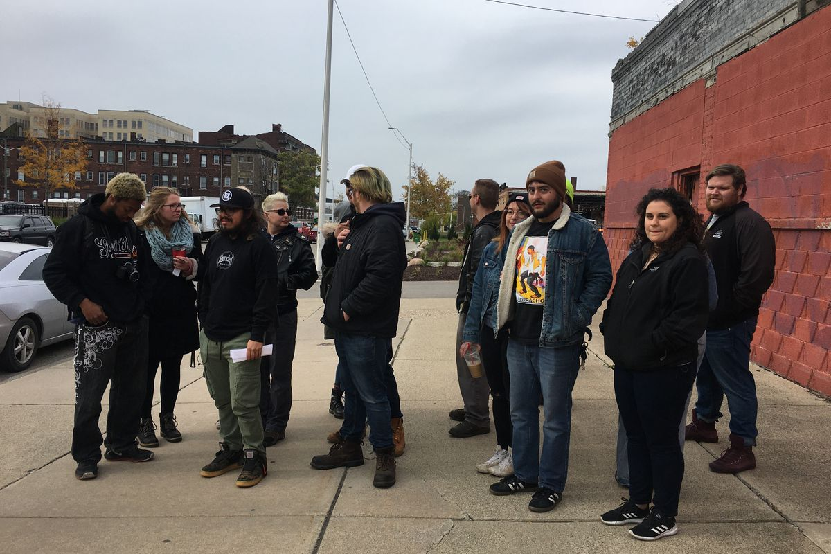A diverse group of staff in sweatshirts and hats gathers near the Founders Detroit taproom in Cass Corridor for a peaceful gathering.