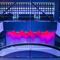 The view from the top bar, looking at the stage and the two-story stripper pole. From below, you can look up at the girls dancing on the second floor's circular lucite stage.