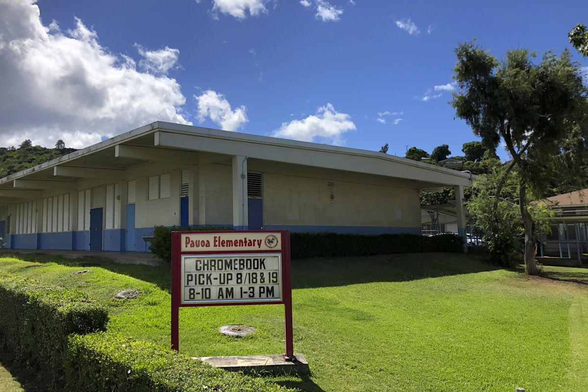 A sign at Pauoa Elementary School in Honolulu on Monday, August 17, 2020, informs students when to pick-up computers for distance learning. Many Hawaii public school students are spending the first day of school online as coronavirus cases surge, mostly on the island of Oahu, where Honolulu is located.