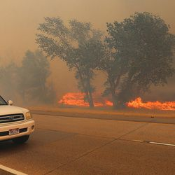 Cars pass the fire as it burns along I-84 near Weber Canyon on Tuesday, Sept. 5, 2017.