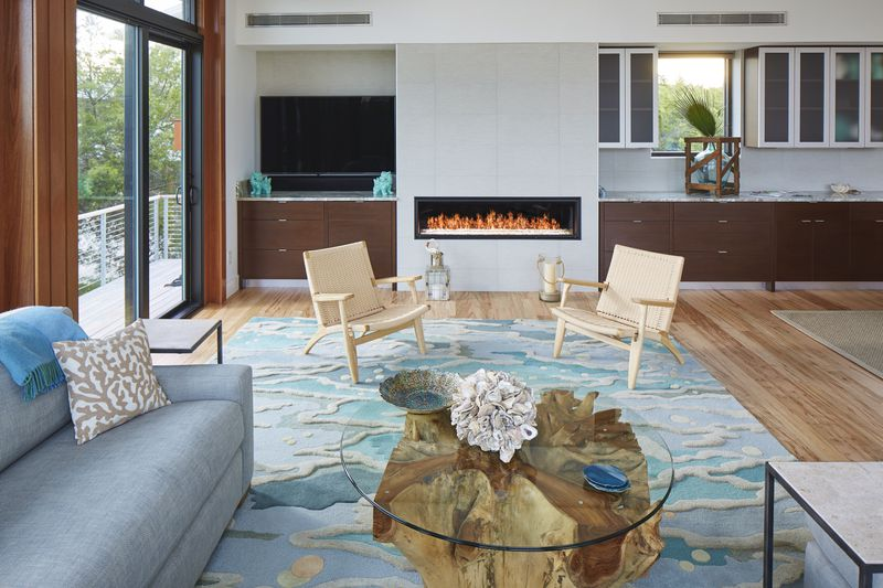A living room features a round glass coffee table, two chairs on a teal rug, and a modern gas fireplace.