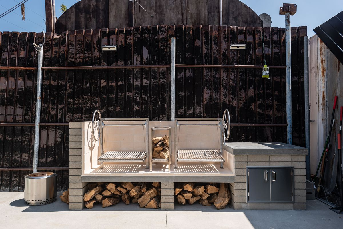 A steel grill and cinder block with wood beneath.