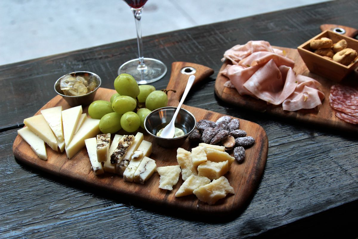 A cheeseboard with different cheeses and grapes