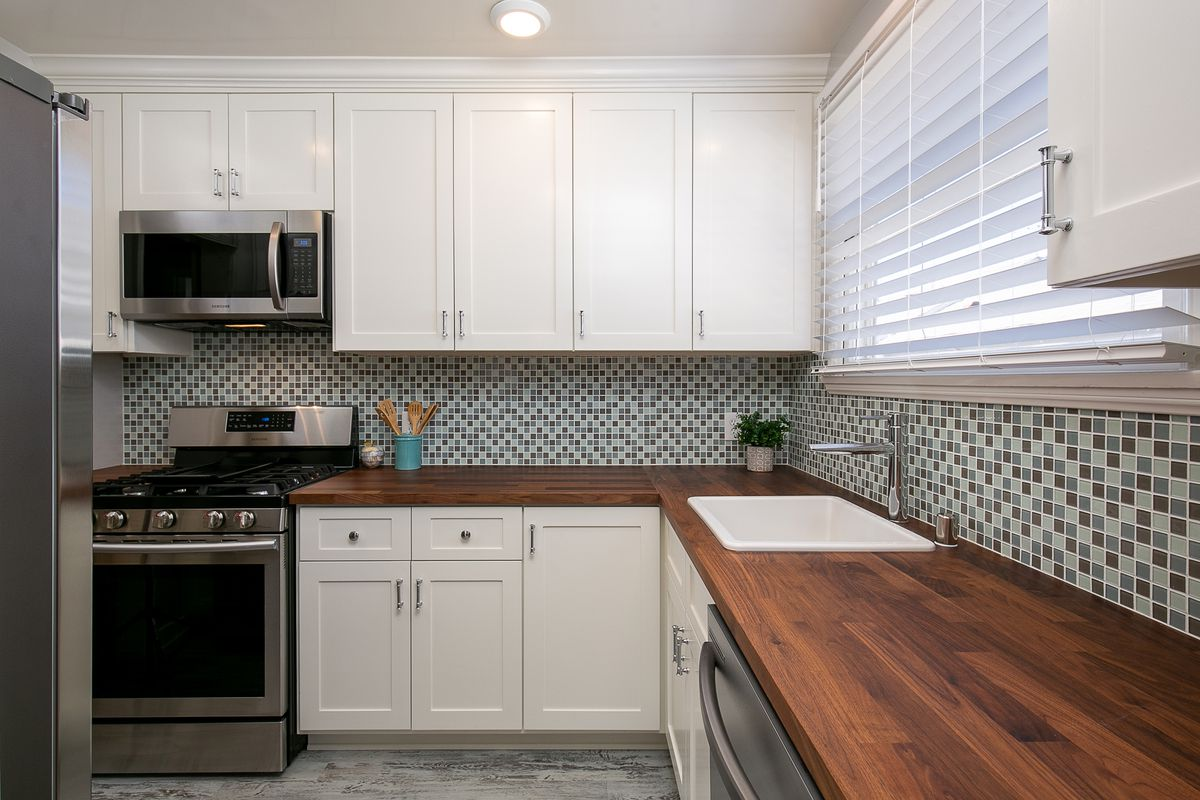 An L-shaped kitchen with dark wood counters and a backsplash of small tiles.