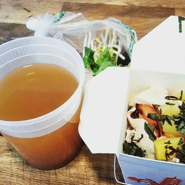 A soup, packed with broth in a plastic container and ingredients in a separate white takeout container.