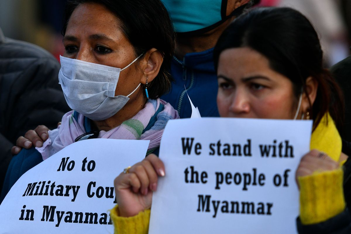 Protesters from the civil society hold placards during a protest in Kathmandu on February 1, 2021, after Myanmar's military seized power in a bloodless coup on Monday, detaining democratically elected leader Aung San Suu Kyi as it imposed a one-year state of emergency.