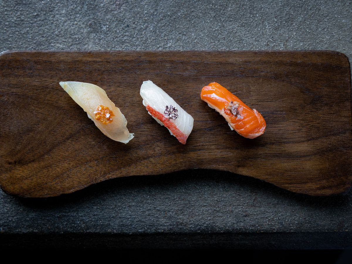 A brown board with three pieces of sushi on it.