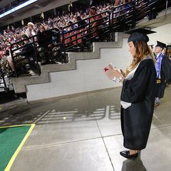 Ashley Baker sends a text before Salt Lake Community College's commencement ceremony at the Maverik Center in West Valley City on Friday, May 6, 2016.