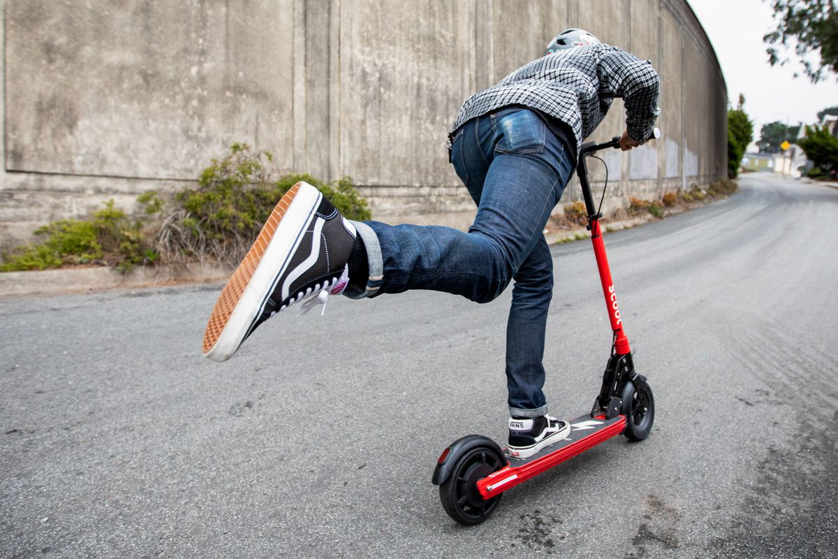 A rider kicking on a red e-scooter.