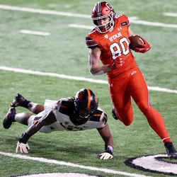 Utah Utes tight end Brant Kuithe (80) runs away from Oregon State Beavers linebacker Avery Roberts (34) as Utah and Oregon State play a college football game at Rice-Eccles Stadium in Salt Lake City on Saturday, Dec. 5, 2020.